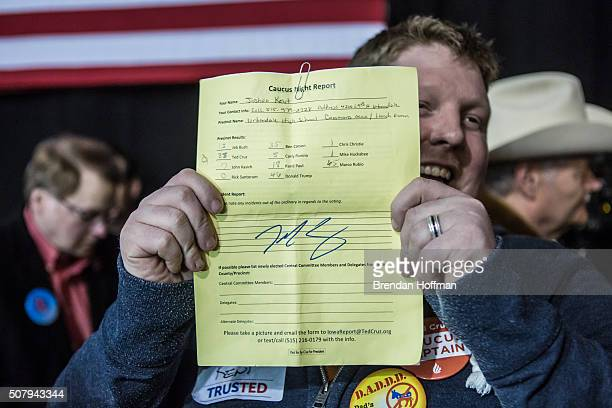 A supporter shows an Iowa caucus report from his precinct signed by Republican presidential candidate Sen Ted Cruz at a caucus night rally on...