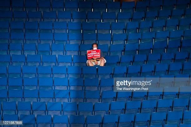 A supporter sits alone in the top sections of seating as Vice President Mike Pence speaks before President Donald J Trump arrives for a Make America...