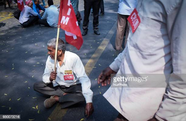 A supporter sits holding the CPI flag as members of the Communist Party of India CPI and other Leftist parties protest against Bhartiya Janta Party...