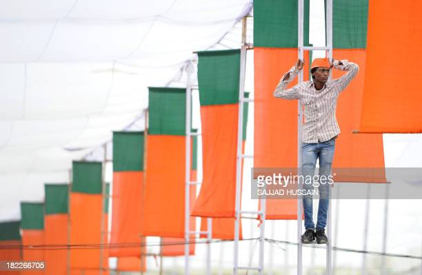 A supporter stands on a pole as he listens to Gujarat state Chief Minister and the Bharatiya Janata Party's prime ministerial candidate Narendra Modi...