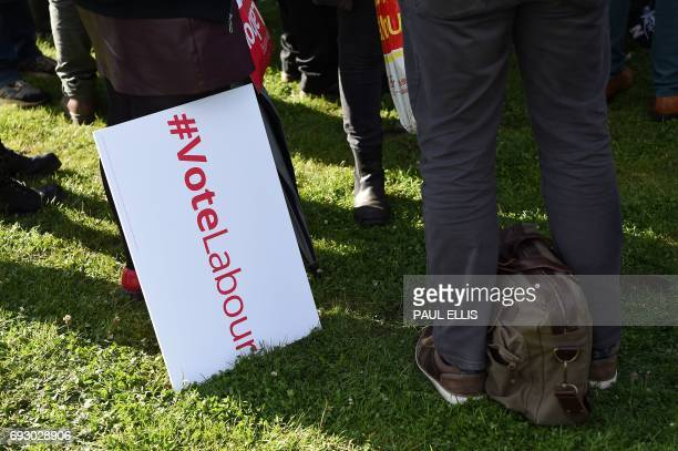A supporter stands with a placard as people wait for Britain's main opposition Labour Party leader Jeremy Corbyn to speak at a general election...