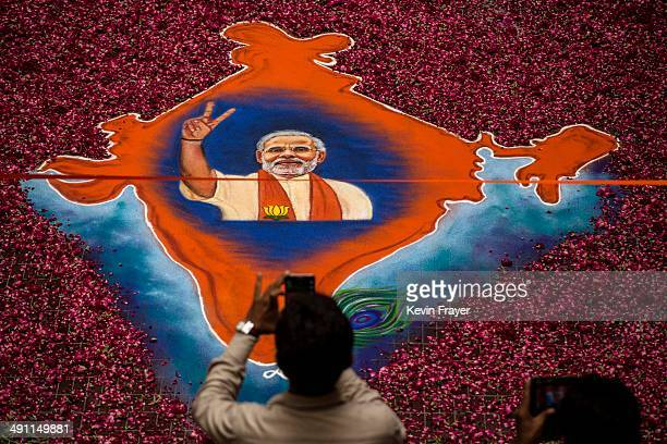 A supporter takes a picture of a map of India made of flowers with a picture of BJP leader Narendra Modi on it at the party's headquarters on May 16...