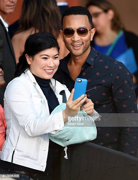 A supporter takes a selfie with singer/songwriter John Legend after his wife model and television personality Chrissy Teigen spoke at a campaign...