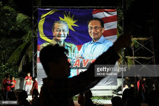 A supporter takes pictures in front of a banner showing former Malaysian Prime Minister Mahathir Mohamad and jailed former opposition leader and...