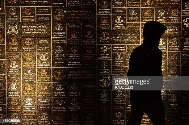 A supporter walks past a memorial wall outside of Goodison Park ahead of the English FA Cup Third Round football match between Everton and West Ham...
