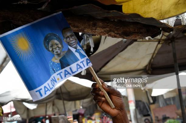 Supporter waves a campaign flag with photographs of incumbent Benin President Patrice Talon and running mate Mariam Talata in the market in Cotonou...