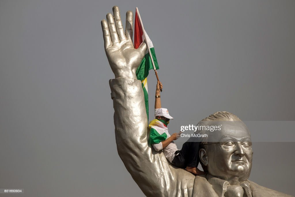 A supporter waves a flag from the stadium statue of Franso Hariri as he waits for the arrival of Kurdish President Masoud Barzani during a rally for the upcoming referendum for independence of Kurdistan on September 22, 2017 in Erbil, Iraq. The Kurdish Regional government is preparing to hold the September 25, independence referendum despite strong objection from neighboring countries and the Iraqi government, which voted Tuesday to reject Kurdistan's referendum and authorized the Prime Minister Haider al-Abadi to take measures against the vote. Despite the mounting pressures Kurdistan President Masoud Barzani continues to campaign and state his determination to go ahead with the vote.