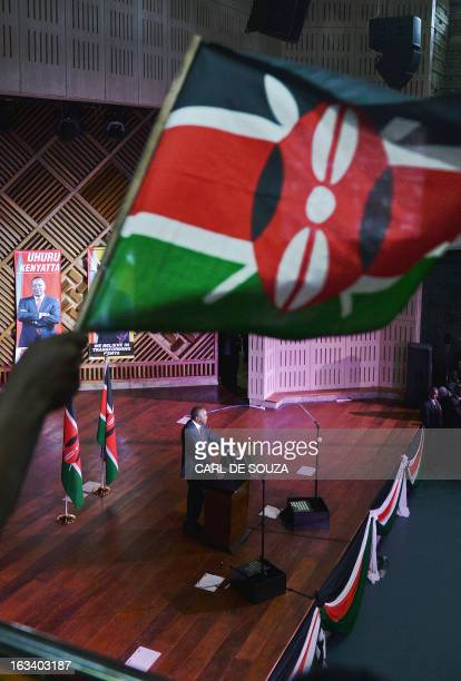 A supporter waves a Kenyan flag as the newly elected President Uhuru Kenyatta delivers a speech following his victory in Kenya's national elections...