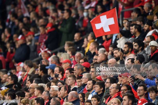 Supporter waves a Swiss flag during FIFA World Cup Qatar 2022 qualification football match between Switzerland and Northern Ireland at the Stade de...