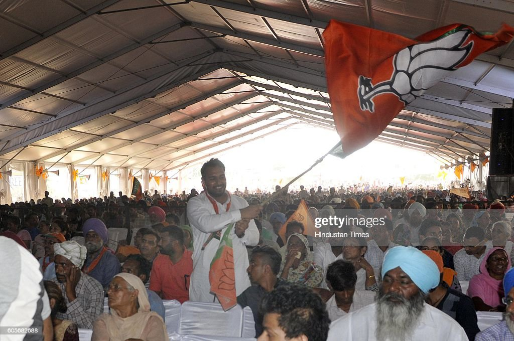 BJP supporter waves the flag as Minister for Road Transport and Highways Shipping Nitin Gadkari and Punjab Deputy CM Sukhbir Singh Badal arrive to...
