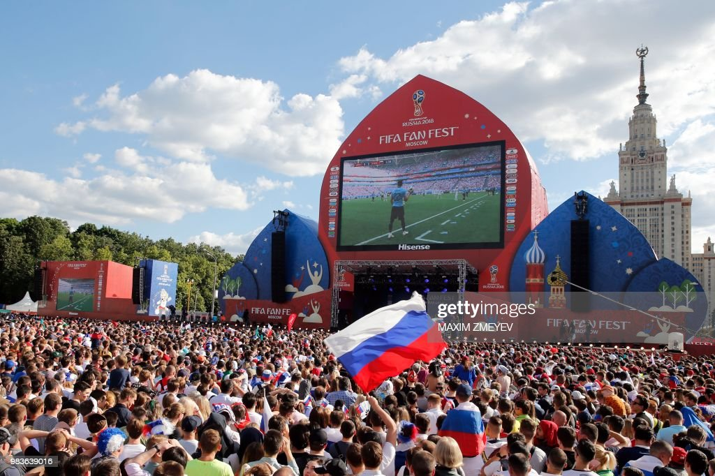 A supporter waves the Russian national flag as Russia and Uruguay's fans watch on a giant screen the Russia 2018 World Cup Group A football match between Uruguay and Russia, at the fan zone in Moscow on June 25, 2018.