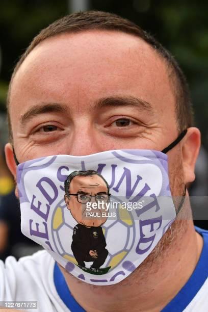 A supporter wearing a Leeds face covering gestures outside their Elland Road ground as fans celebrate the club's return to the Premier League after a...