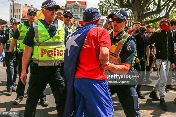 UPF supporter wearing an Australian flag around his neck is pushed back by police as he is taunted by antifascist protestors during a protest...