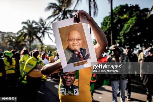 TOPSHOT A supporter wearing the colours of the African National Congress and holding a portrait of former South African president Jacob Zuma takes...