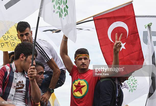 A supporter wears a Kurdish protester holds a Kurdistan Workers' Party flag as he waves Turkish flag during Turkey's proKurdish People's Democtratic...