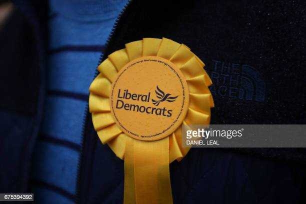 TOPSHOT A supporter wears a party rosette as he listens to Britain's Liberal Democrats leader Tim Farron speak at the start of his battle bus tour in...