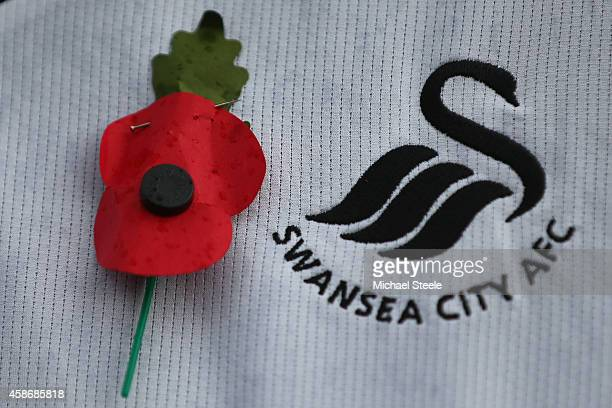 A supporter wears a poppy next to the club crest of Swansea City during the Barclays Premier League match between Swansea City and Arsenal at the...