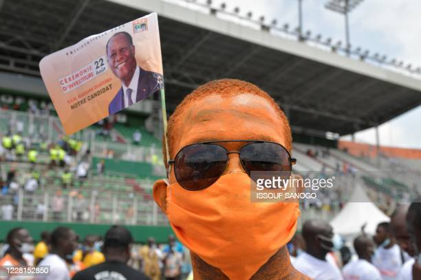 TOPSHOT A supporter with a flag poses for a photograph as Ivory Coast's president Alassane Ouattara speaks at the Felix HouphouetBoigny stadium on...