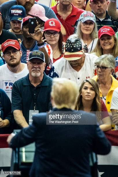 """Supporter with a QAnon hat listens as President Donald J. Trump walks out to speak at a """"Keep America Great Rally"""" at U.S. Bank Arena on Thursday,..."""