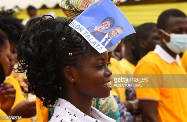 Supporter with an electoral campaign flyer of the incumbent President Patrice Talon and running mate Mariam Talata, looks on, during a campaign rally...