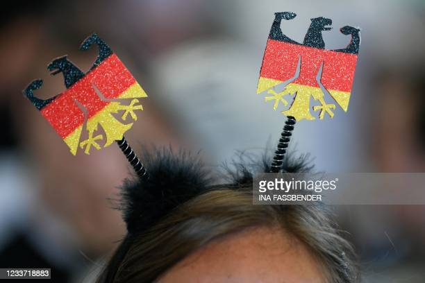 Supporter with German Eagles in her hair, watchs the UEFA EURO 2020 round of 16 football match between England and Germany at the Grugapark in Essen,...