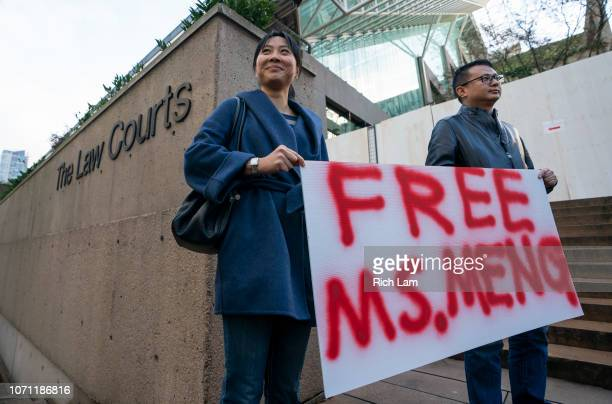 Supporters Ada Yu and Wade Meng stand with a sign outside BC Supreme Court before the bail hearing for Huawei Technologies CFO Meng Wanzhou on...