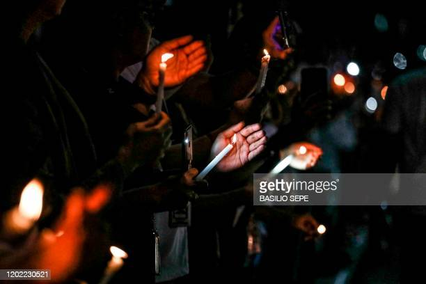 Supporters and employees of ABS-CBN, the country's largest broadcast network, hold candles as they join a protest in front of the ABS-CBN building in...