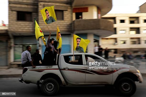 Supporters and fighters of the Syrian Kurdish People's Protection Units drive in the street in Qamishli waving flags bearing the portrait of jailed...