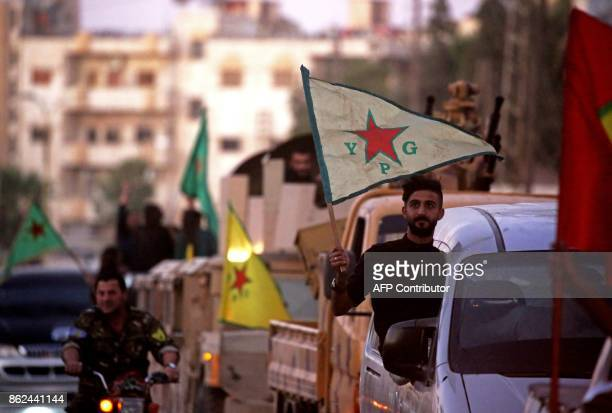 Supporters and fighters of the Syrian Kurdish People's Protection Units drive in the street in Qamishli waving flags as they celebrate after the...
