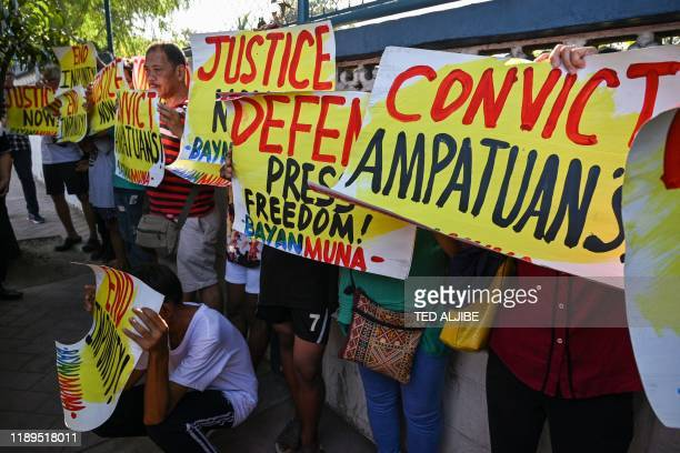 Supporters and journalists hold a rally in front of the gate of the capital command headquarters in Manila on December 19 ahead of a court verdict on...