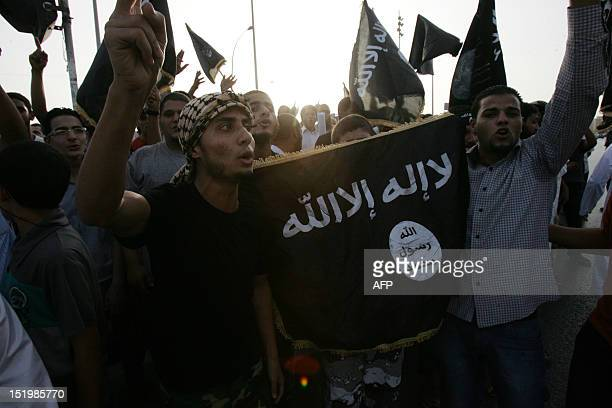 Supporters and members of hardline Islamist group of Ansar alSharia shout slogans as they hold an AlQaeda affiliated flag during a demonstration...