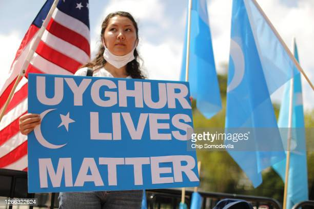 Supporters and members of the East Turkistan National Awakening Movement rally outside the White House to urge the United States to end trade deals...