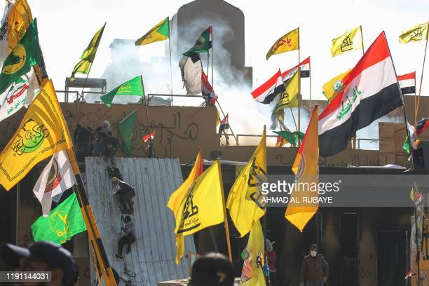 Supporters and members of the Hashed alShaabi paramilitary force try to scale a wall of the US embassy in the Iraqi capital Baghdad on January 1 2020...