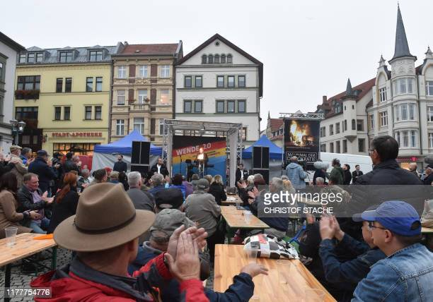 Supporters applaud as Bjoern Hoecke, top candidate of the far-right Alternative for Germany party for regional elections in Thuringia, speaks on the...