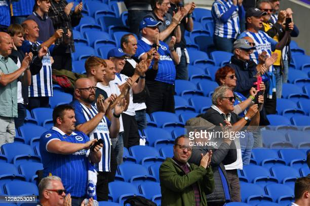 Supporters applaud the teams from their sociallydistanced seats ahead of the preseason friendly football match between Brighton and Hove Albion and...