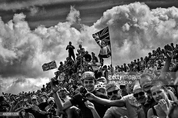 Supporters are pictured along the road during the 201 km second stage of the 101st sedition of the Tour de France cycling race on July 6 2014 between...