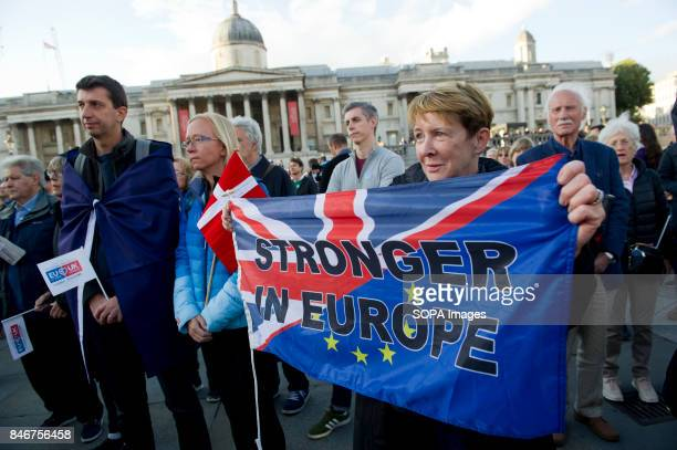 Supporters are pictured while holding a banner with the UK and EU flags writting on it 'Stronger in Europe' during The Citizens' Rally as a day of...