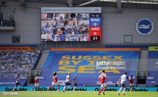 Supporters are seen on the scoreboard as play goes on during the English Premier League football match between Brighton and Hove Albion and Arsenal...
