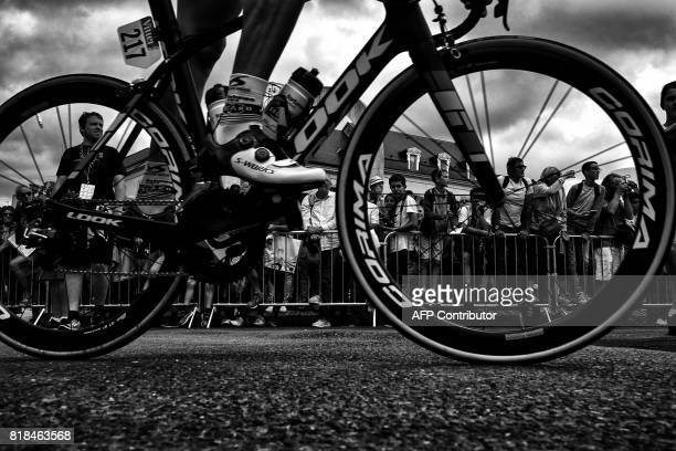 Supporters are seen through wheels prior to the 178 km tenth stage of the 104th edition of the Tour de France cycling race on July 11, 2017 between...