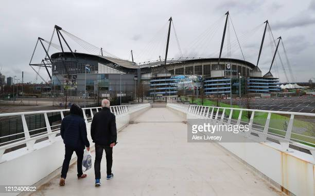 Supporters are seen walking outside the Etihad Stadium home of Manchester City FC as the scheduled match to be played today between Manchester City...