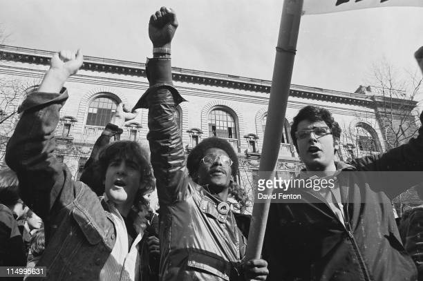 Supporters at a rally for Black Panthers Bobby Seale and Erica Huggins raise closed fists in a power salute New Haven CT April 30