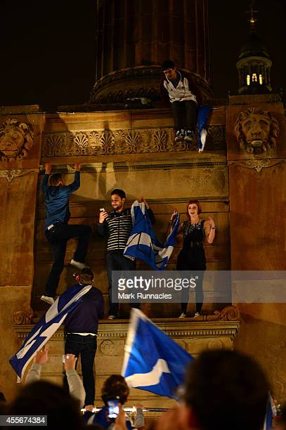 Supporters at a Yes rally in George Square climb a monument on September 19 2014 in Glasgow Scotland Polls have now closed in the Scottish referendum...