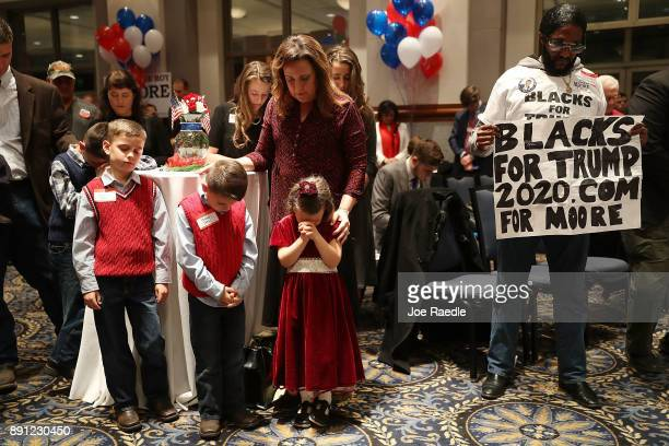 Supporters bow their heads in prayer as they await the arrival of Republican Senatorial candidate Roy Moore for his election night party in the RSA...