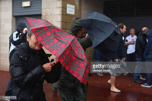 Supporters brave the torrential rain as they arrive ahead of the Barclays Premier League match between Swansea City and Manchester United at the...