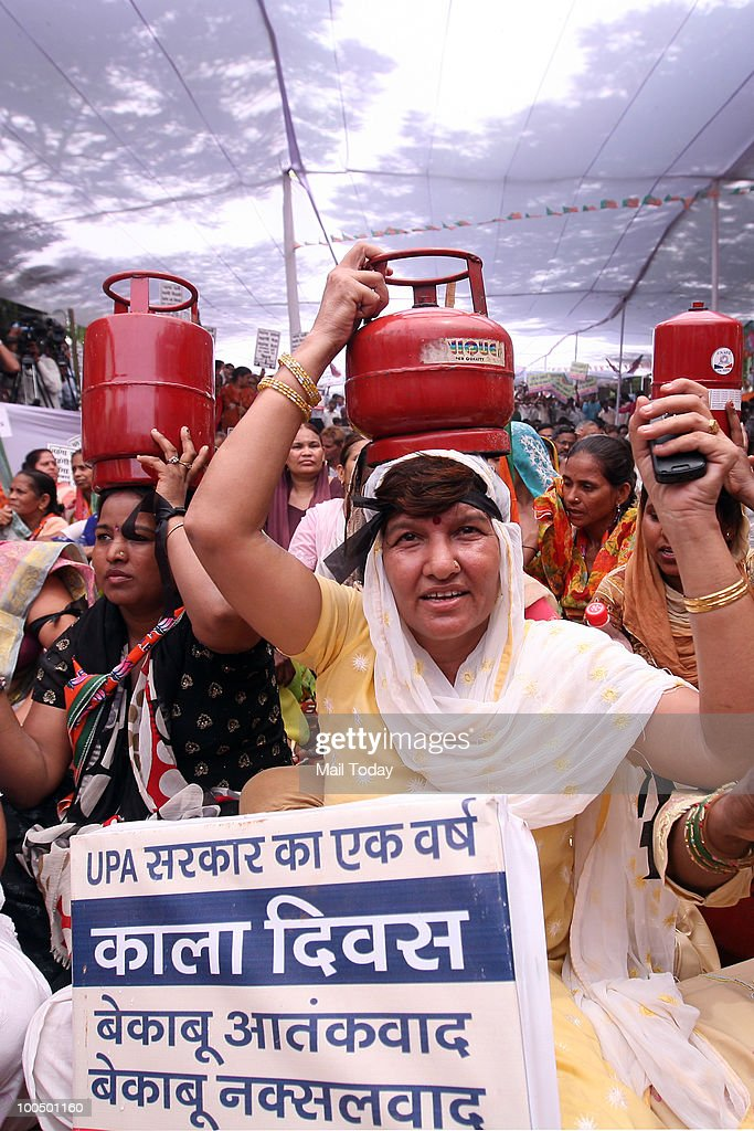 BJP supporters carry cooking gas cylinders at a BJP rally to observe 'Black Day' on completion of one year by the UPA government in New Delhi on May 24, 2010.