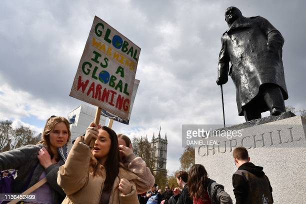 Supporters carry placards as they gather to attend the YouthStrike4Climate demonstration in Parliament Square central London on April 12 2019