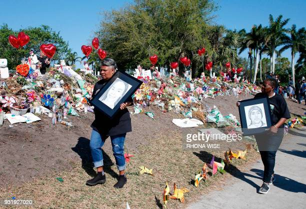 Supporters carry sketches of two of the victims in front of a makeshift memorial in front of Marjory Stoneman Douglas High School as staff teachers...