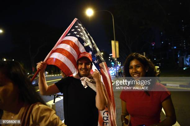 Supporters carrying a US flag wait along the street in the hopes to see US President Donald Trump as he arrives to his hotel in Singapore on June 10...
