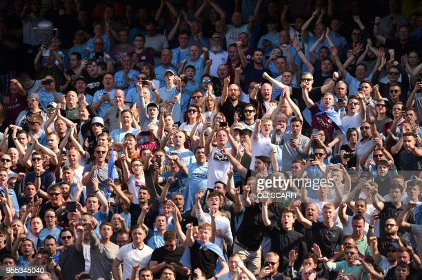 Supporters celebrate as Manchester City's captian Belgian defender Vincent Kompany lifts the Premier League trophy on the pitch after the English...