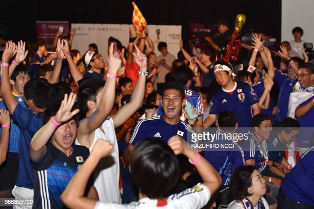 TOPSHOT Supporters celebrate Japan's qualifying while watching Japan's third World Cup football match in Group H against Poland at a public viewing...